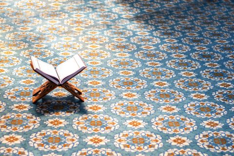 Coran ouvert sur support en bois sur tapis à motifs colorés